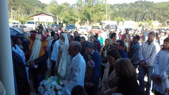 Leigos entrando na igreja, com os padroeiros das comunidades.